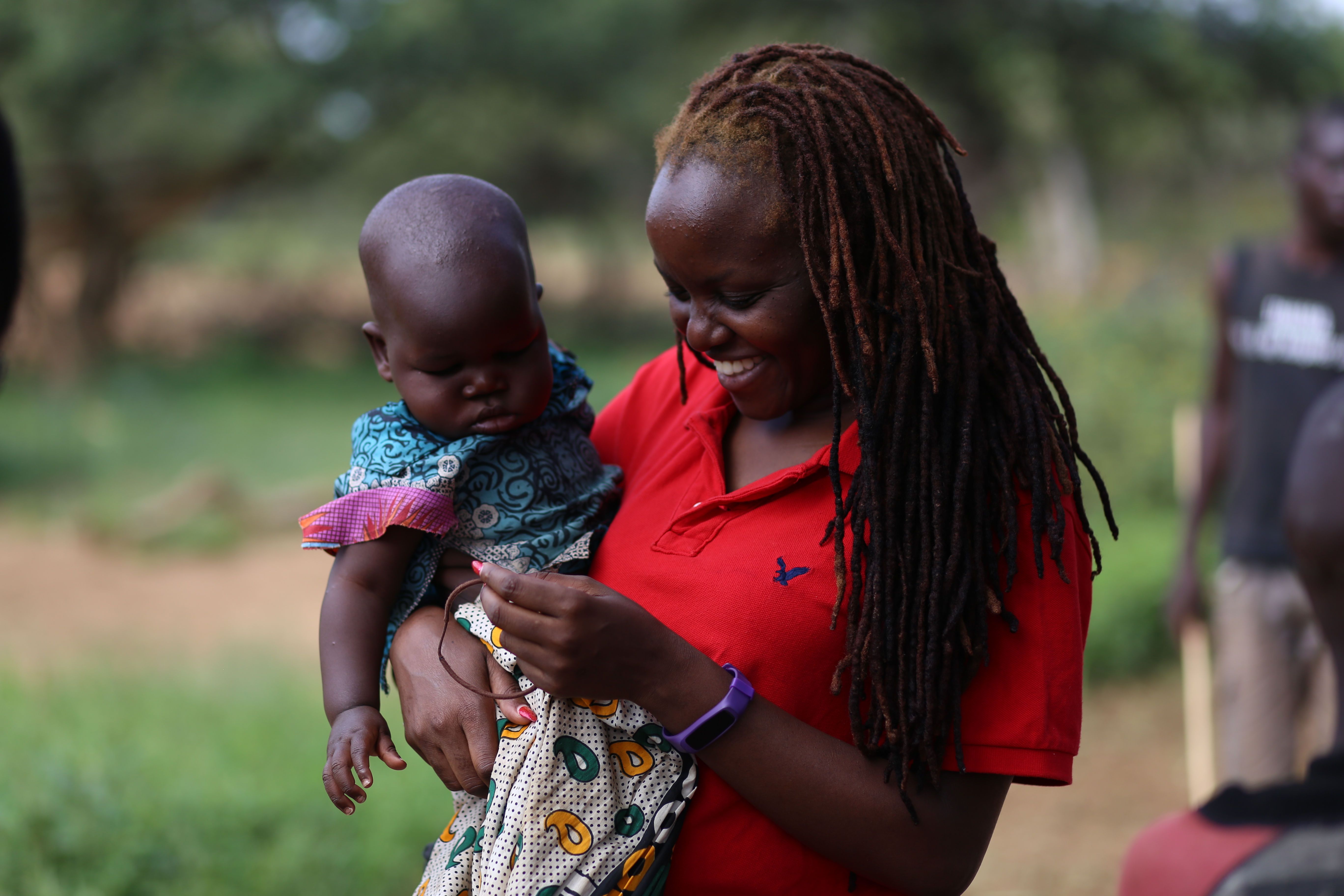Okeyo holds a baby in West Pokot County