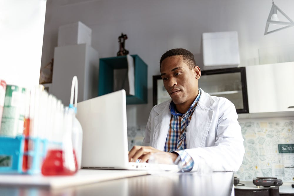 A man in a lab coat types on a computer