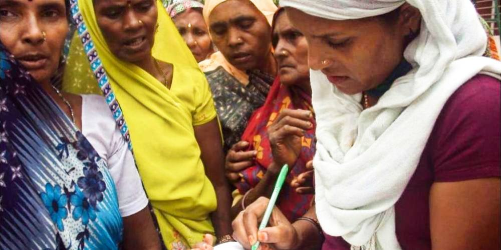 A reporter for Khabar Lahariya interviews a group of women