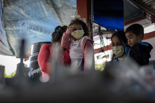 Migrant parents and children at a migrant shelter in Tijuana, Mexico, wear surgical masks to protect against contracting COVID-19 (credit: Christian Monterrosa).