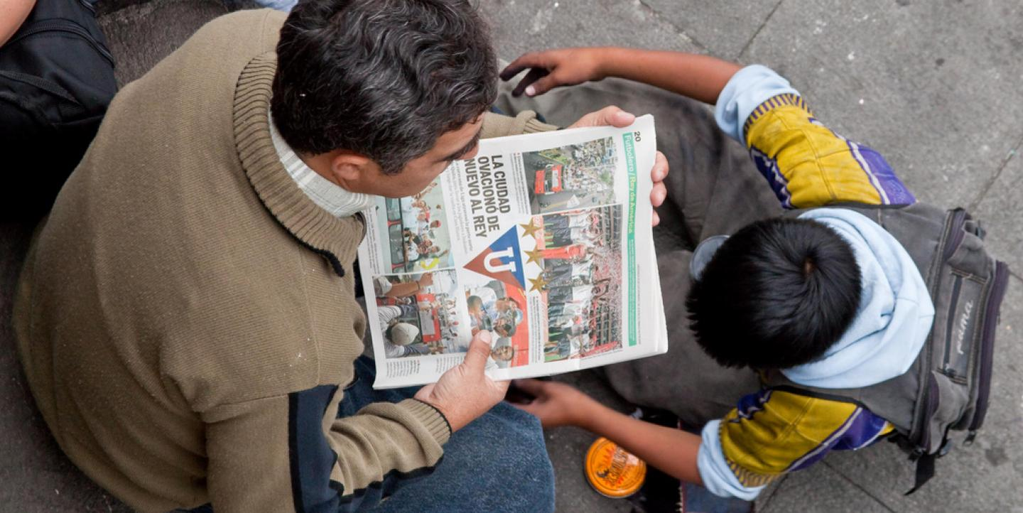 Man and child look at newspaper