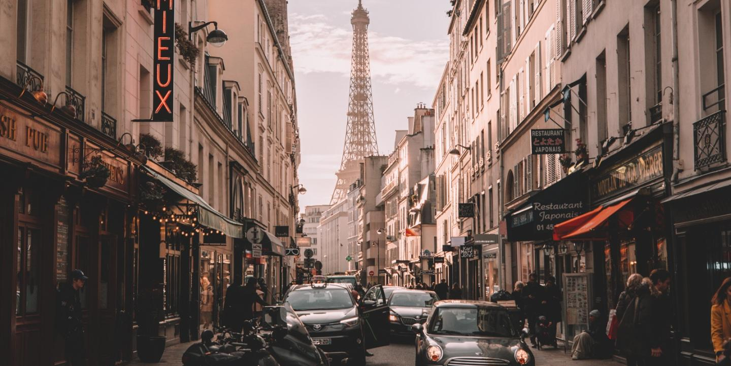 View of the Eiffel Tower through a crowded city street