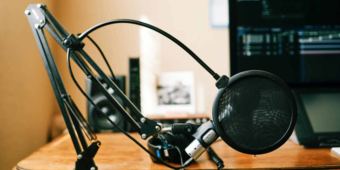 Podcasting equipment, including a microphone, pop filter, mic stand and editing software