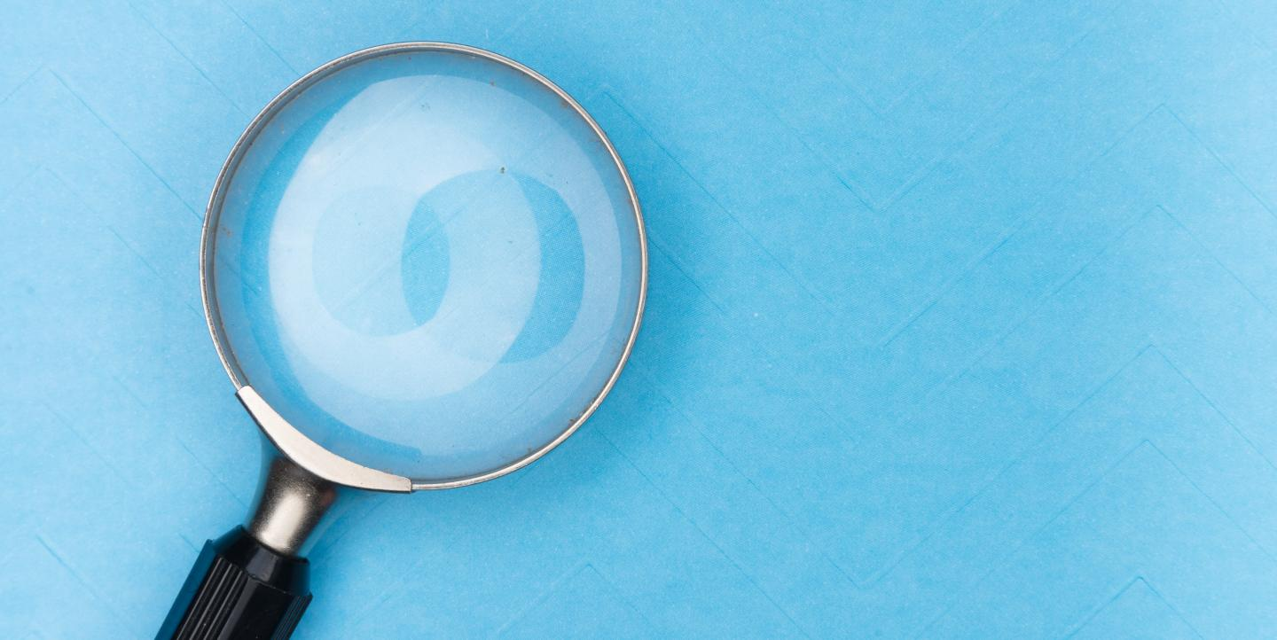 Magnifying glass against a blue background