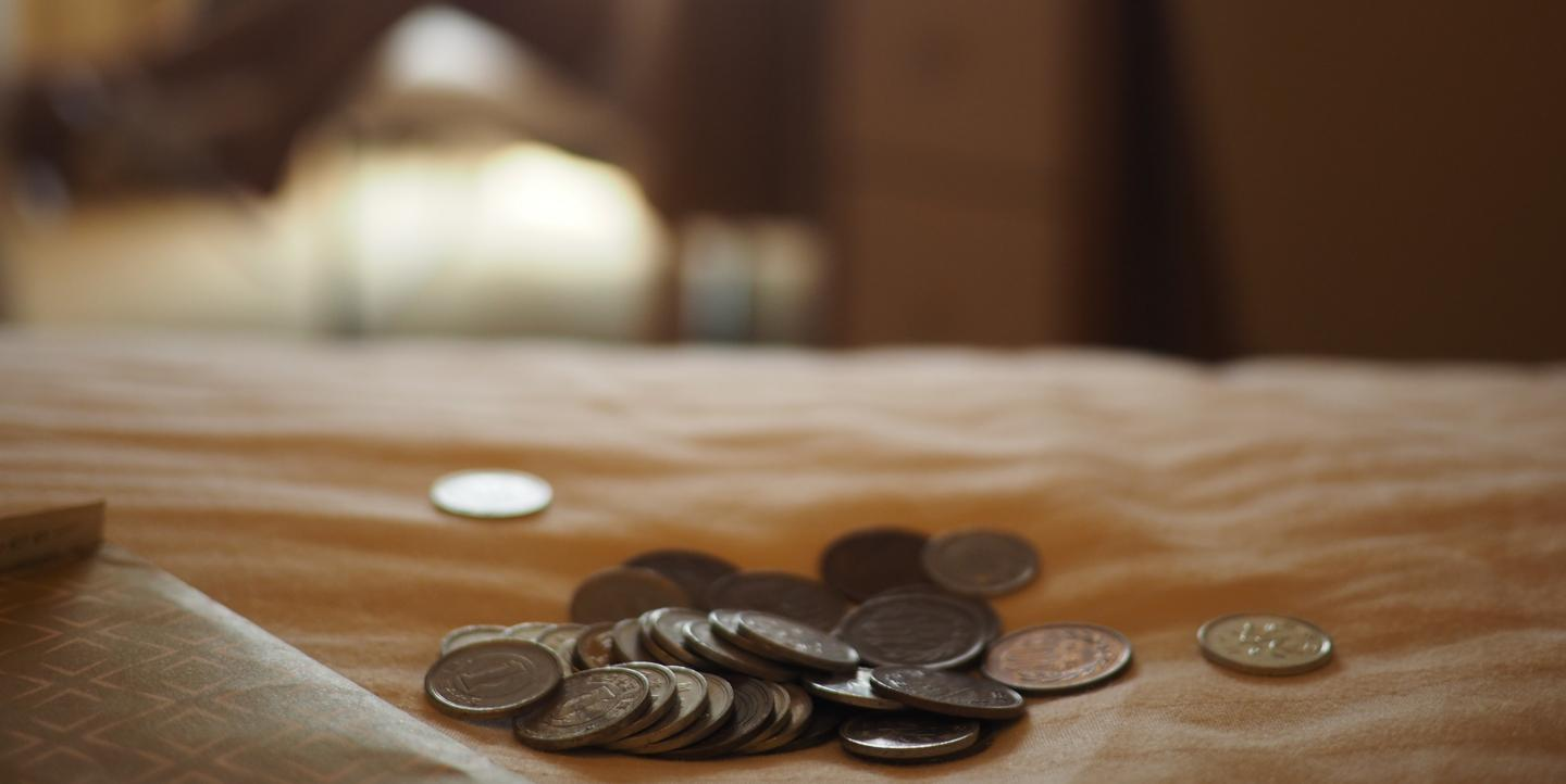 Coins spilled on a brown wooden table
