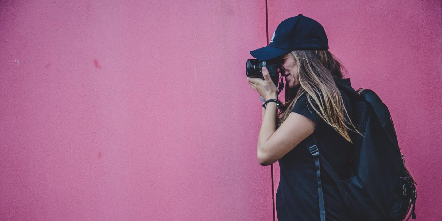 Woman photographer in front of a pink wall