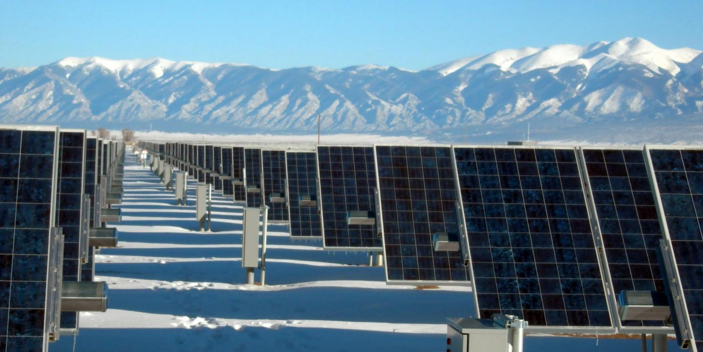 Rows of solar panels on snowy ground in front of mountains