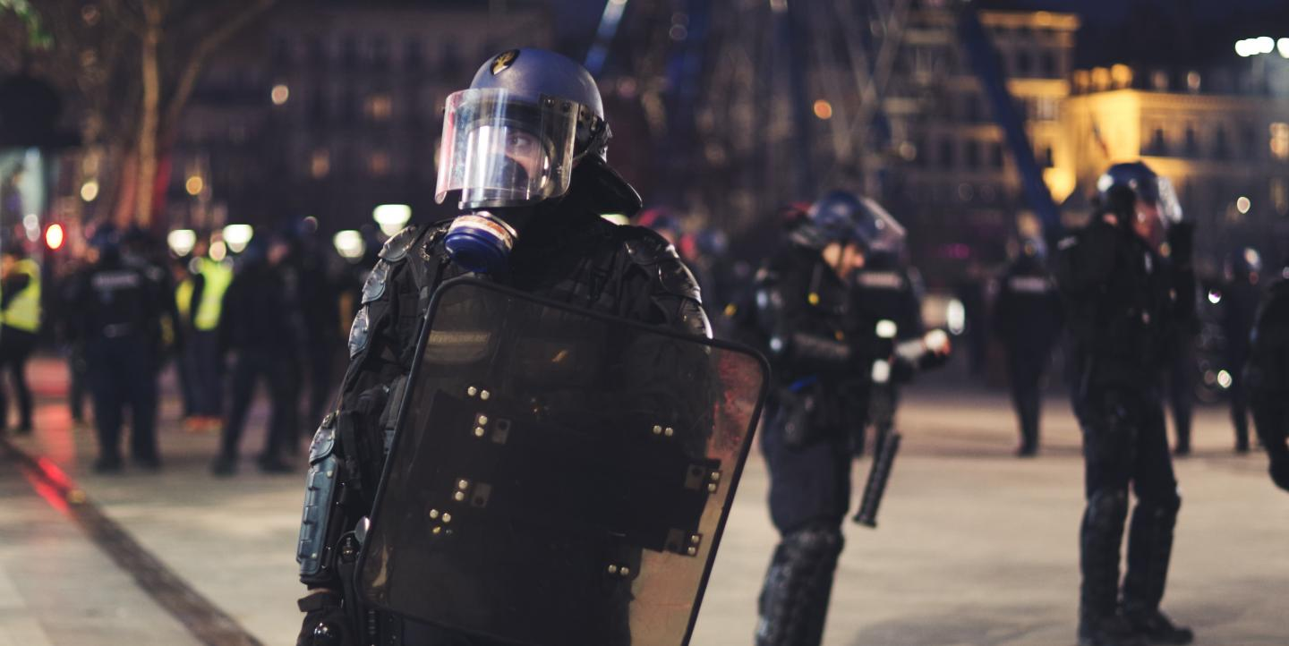 Police officer standing in full riot gear in France