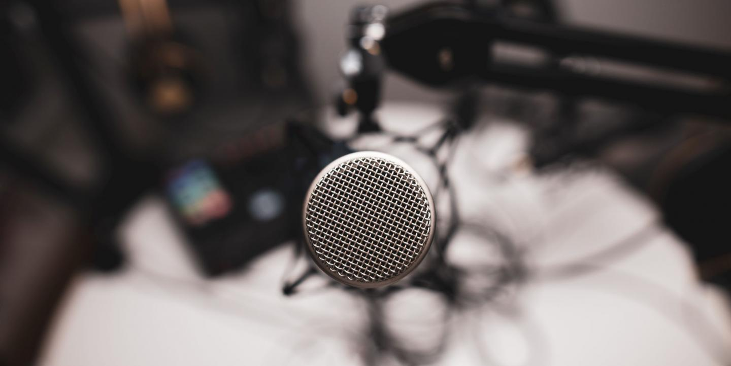 A head-on shot of a professional microphone used for podcasting