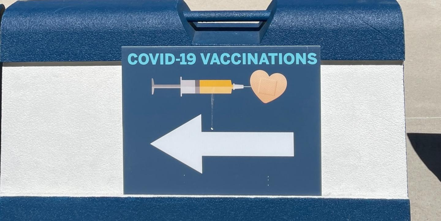 "Sign reads: ""COVID-19 vaccinations"" with an arrow"