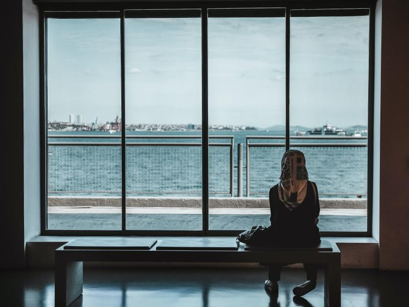 Woman sits alone looking out a large window
